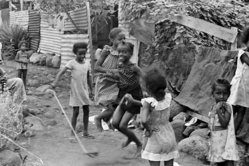 Dans un décor de sable, de rocaille et de tôles rafistolées, la joie à l'état pur…Sommes nous au moment du « bouillon » où le rythme de la corde s'accélère ? Magie de la photographie qui fixe l'instant où l'enfant échappe pour une fraction de seconde aux lois de la pesanteur…