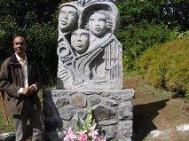 Le père Karl devant la stèle-souvenir en granit des jeunes malgaches du village de la Ressource (1848-1872).